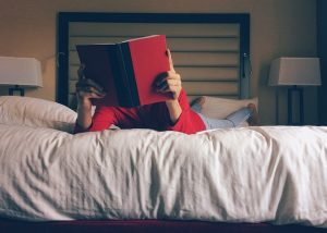 child reading on a clean hotel bed